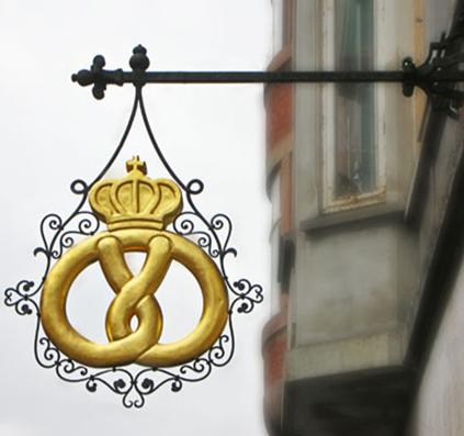 Restaurering af gammelt lauskilt. Kringlen er belagt med bladguld. Store Kongensgade i København. Montereret af Skiltefabrikken